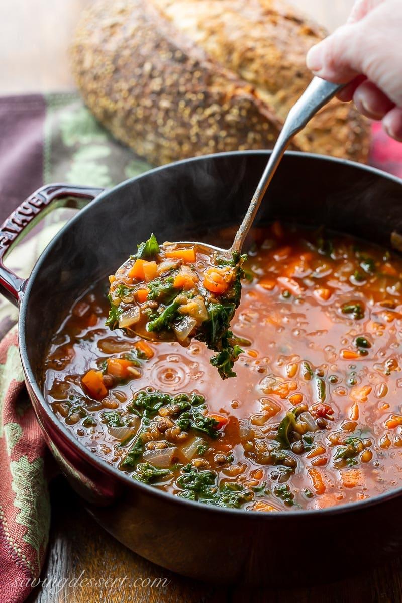 A pot of hot lentil soup being ladled into a bowl