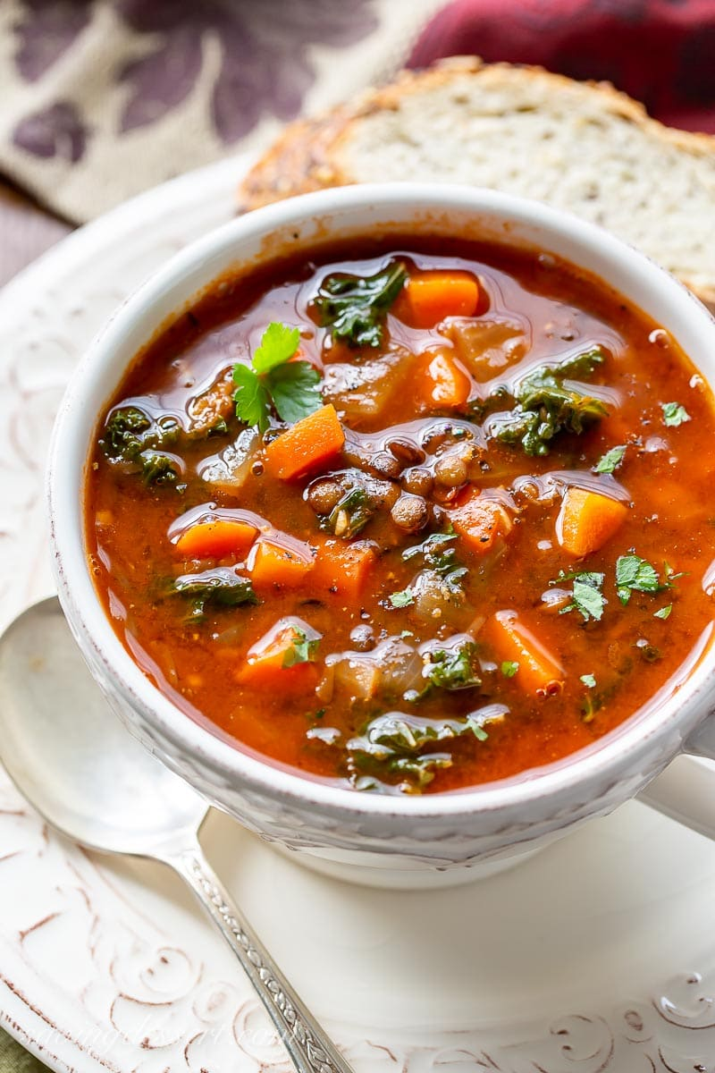 A bowl of soup with carrots, lentils and kale