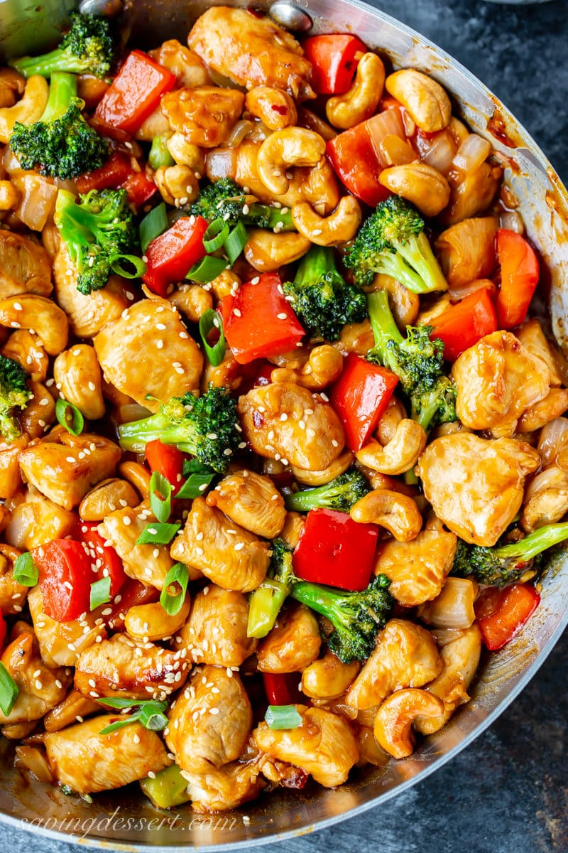 Overhead view of a skillet with Honey Cashew Chicken. Loaded with cashews, red bell pepper, broccoli, onions and garnished with green onions and sesame seeds