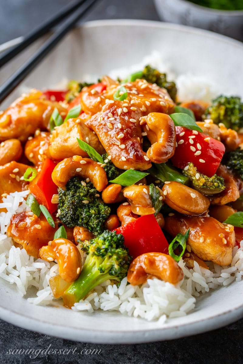 Up close view of a bowl of Jasmine rice topped with Honey Cashew Chicken with red bell pepper, broccoli, onions and cashews. Garnished with sliced green onions and sprinkled with sesame seeds.