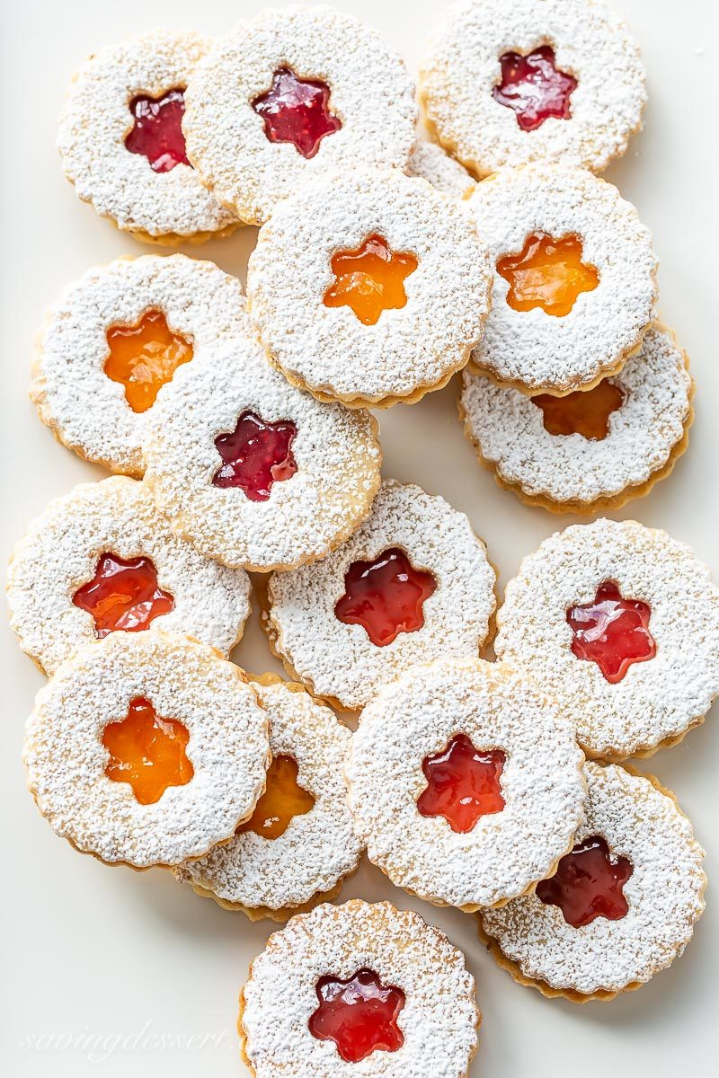 A platter of Linzer cookies filled with jam and topped with powdered sugar