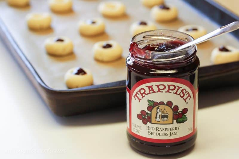 A jar of raspberry jam and cookie dough balls with jam