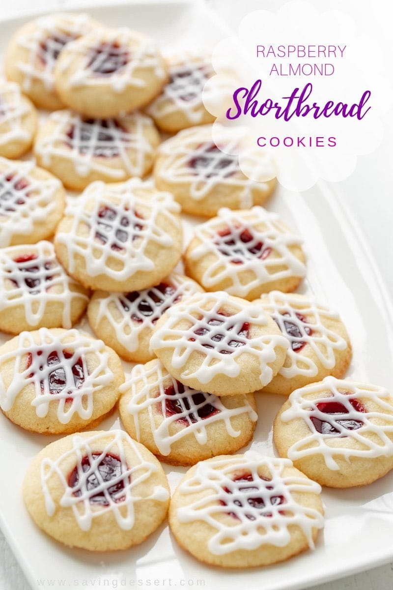 Raspberry Almond Shortbread Thumbprint Cookies - a tender shortbread cookie packed with raspberry jam and topped with a simple almond flavored icing. Not just for the holidays, these are delicious cookies and a family favorite! #savingroomfordessert #cookies #raspberryalmondshortbreadthumbprint #thumbprint #cookies #holidaycookies #holidaybaking #shortbread #raspberry