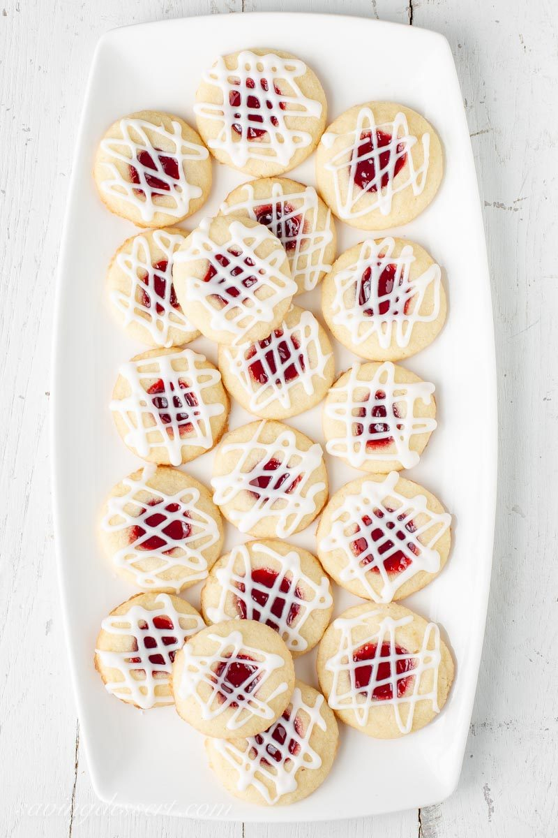 A plate of raspberry almond shortbread thumbprint cookies with a drizzled almond icing