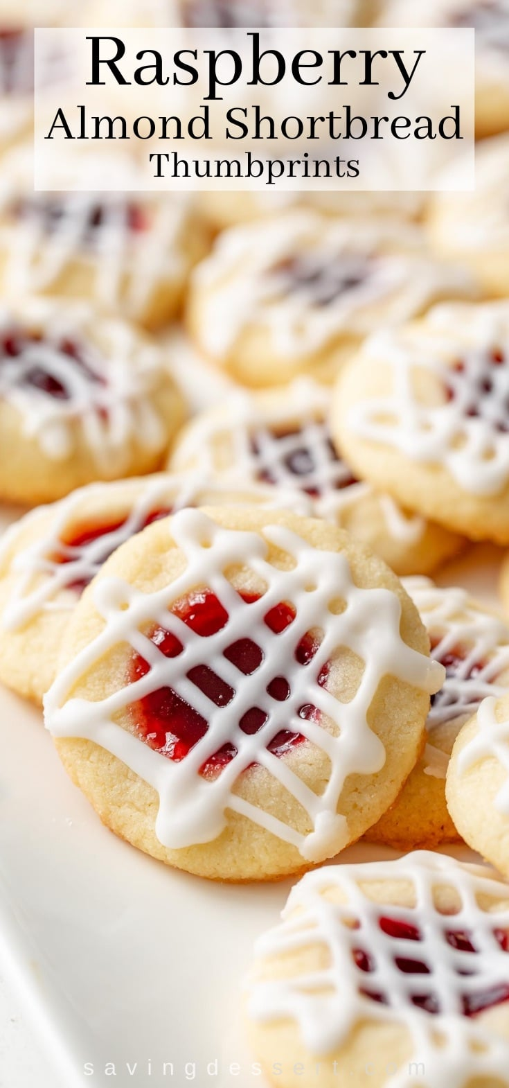 A closeup of a tray of thumbprint cookies filled with raspberry jam topped with a drizzle of icing