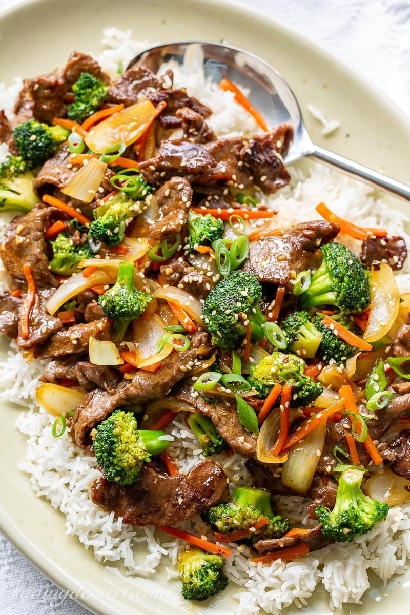 A platter with rice, beef, broccoli, onions and carrots