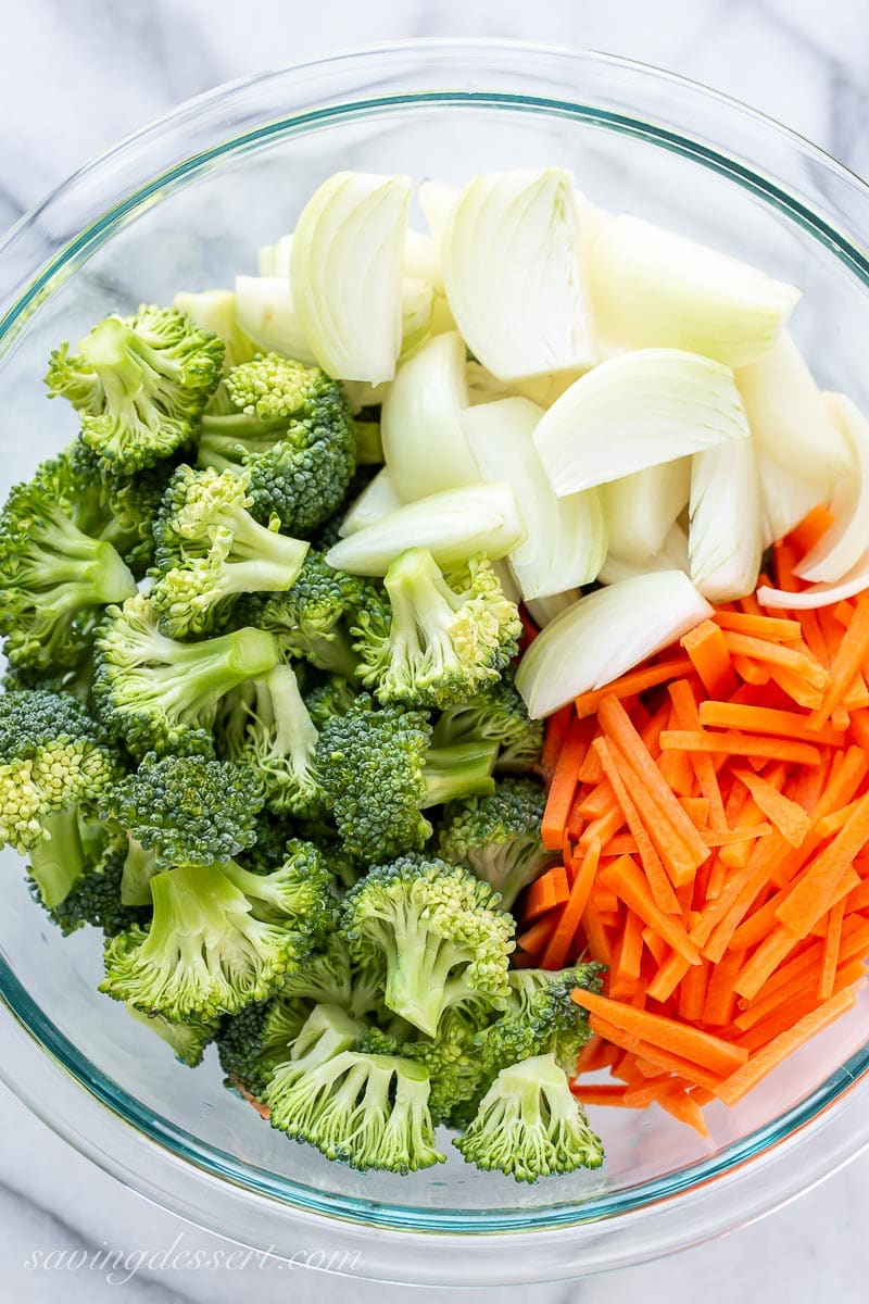 A bowl of raw broccoli, onions and carrot cut into matchsticks