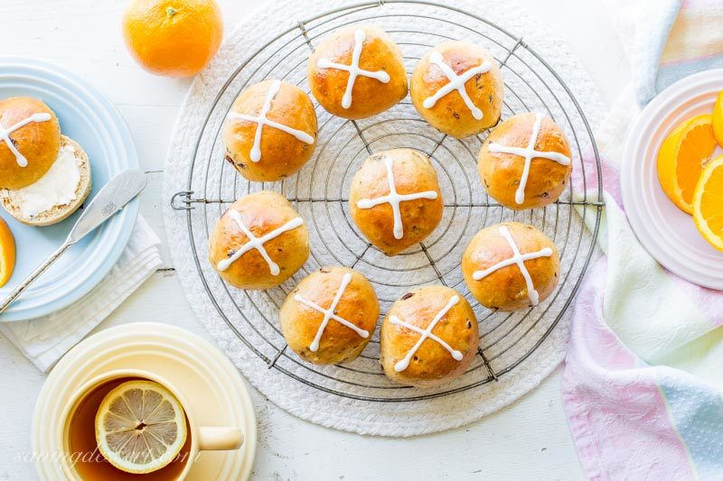 homemade hot cross buns with orange slices and a cup of tea