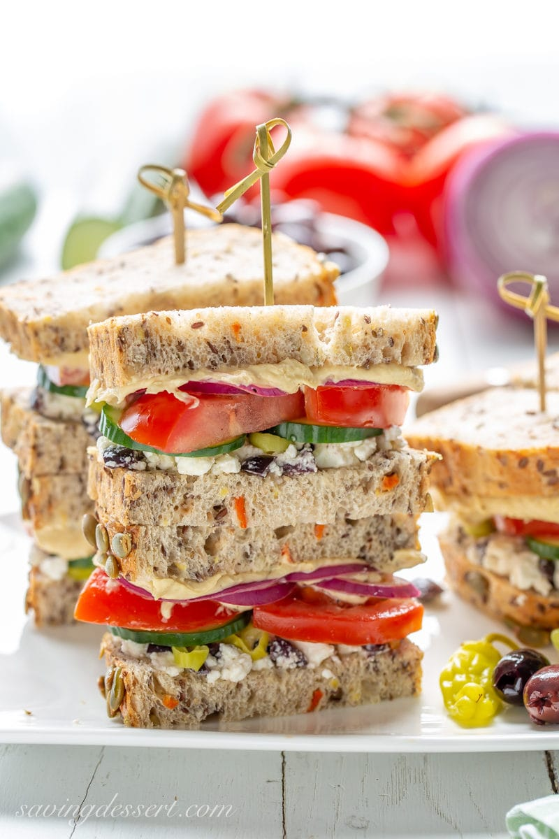 A stack of Greek Salad Hummus Sandwiches with cucumbers, tomatoes, onion, feta and olives on a nice seeded bread.