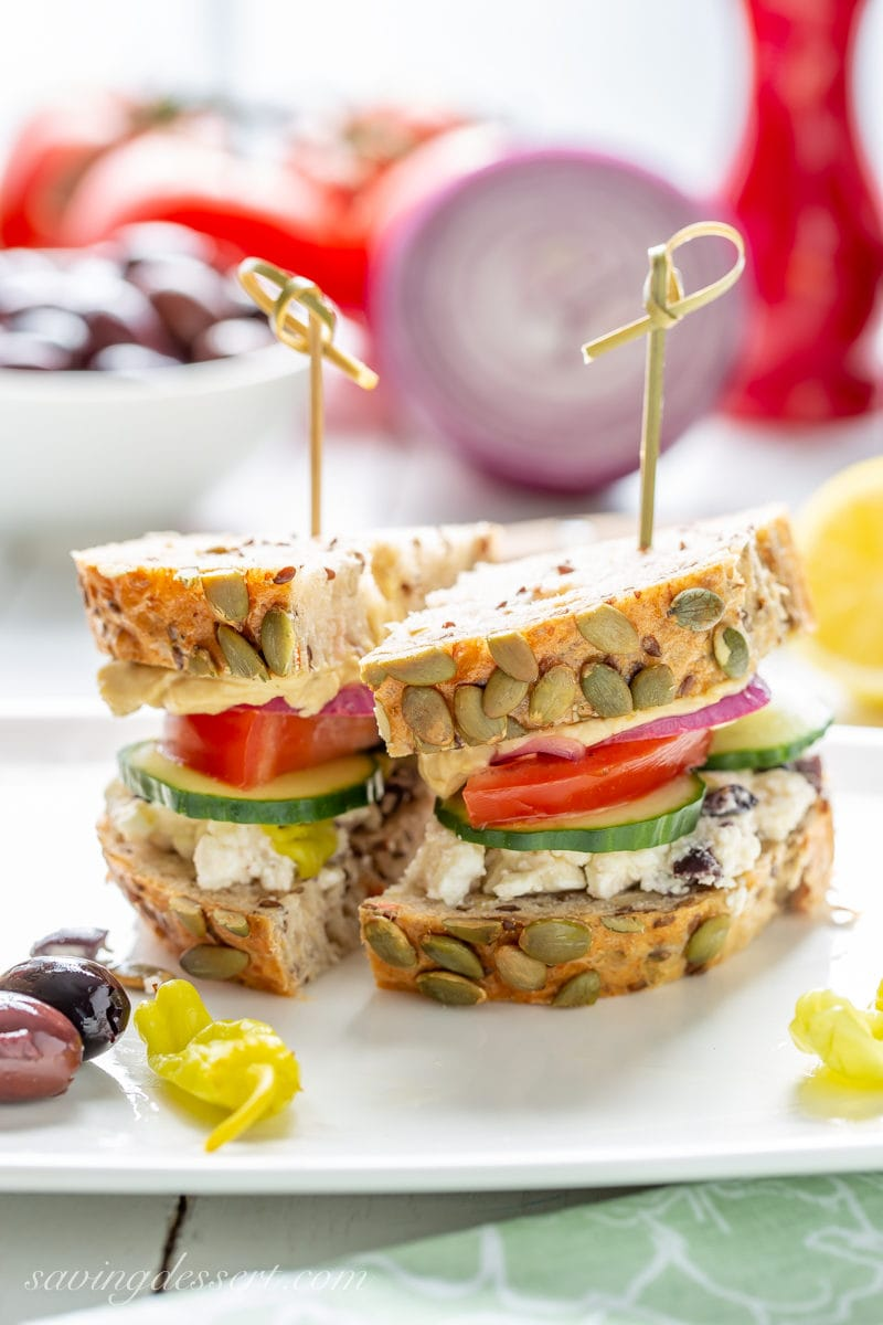 A Greek Salad Hummus Sandwich sliced in half served with peppers and olives