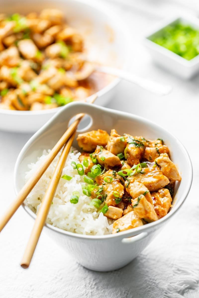 A bowl of Spicy Basil Chicken with Jasmine rice and sliced green onions with chop sticks.