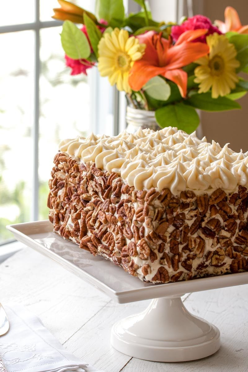 Carrot cake covered with pecans and cream cheese icing