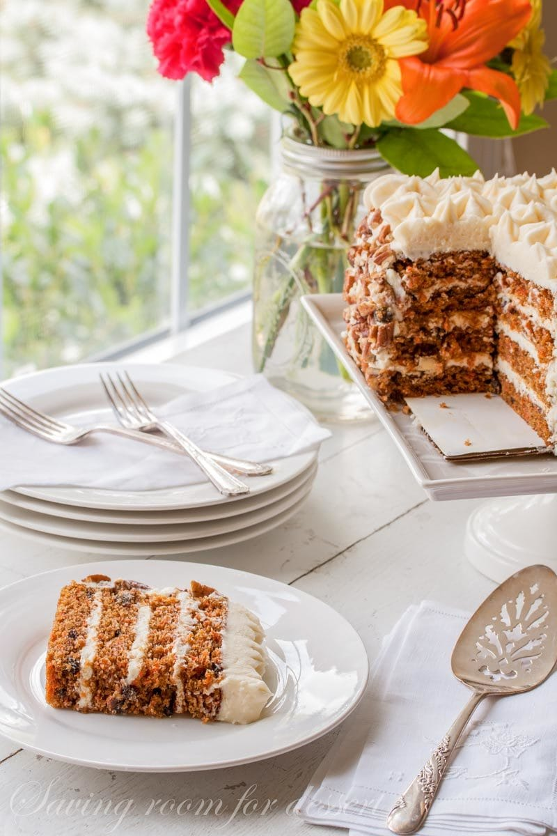 a slice of carrot cake with toasted pecans and cream cheese icing