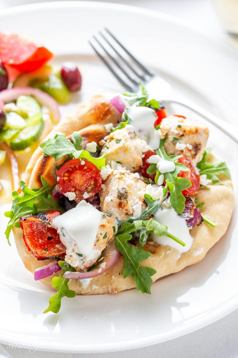A pita sandwich with grilled chicken, tomatoes, arugula, grilled peppers and onions drizzled with a lemon yogurt sauce
