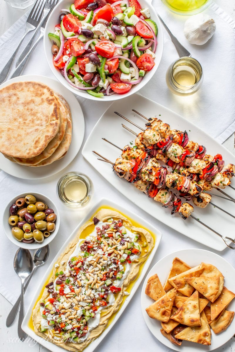 A table with Greek Salad, homemade pita bread, grilled Greek Chicken Kabobs, baked pita chips, olives, and a Greek layered dip