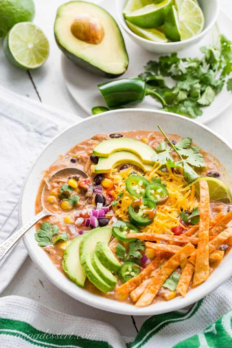 Cream Taco Soup with chicken and topped with avocado, cheese and lime
