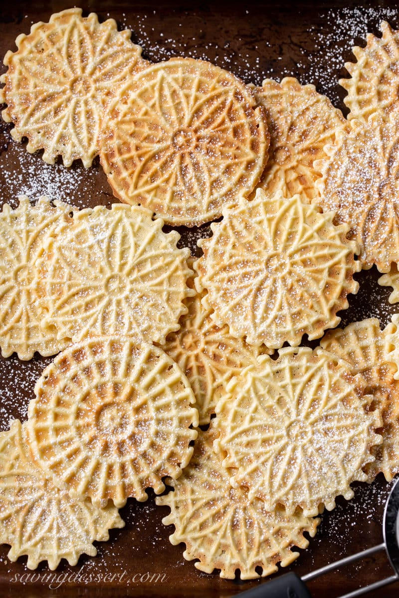 A cookie sheet covered in pizzelle cookies dusted with powdered sugar
