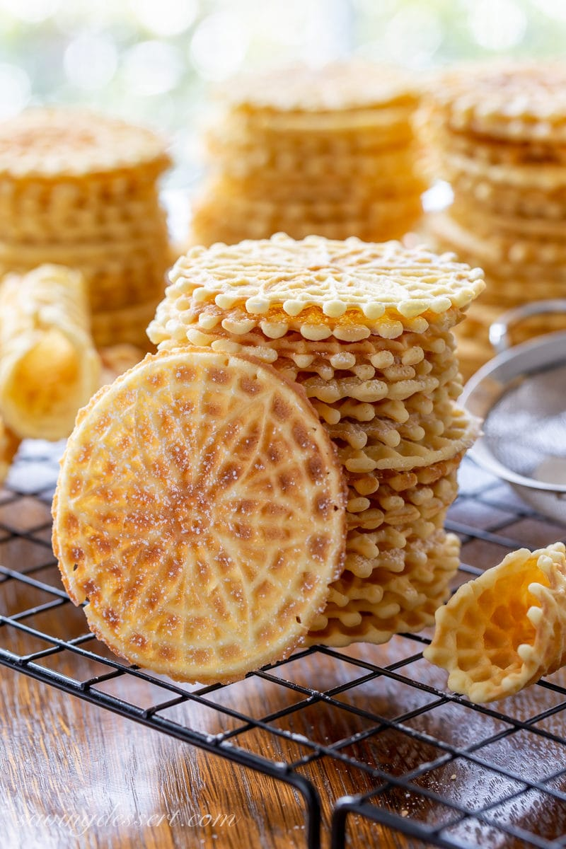 A stack of anise flavored pizzelle cookies on a cooling rack