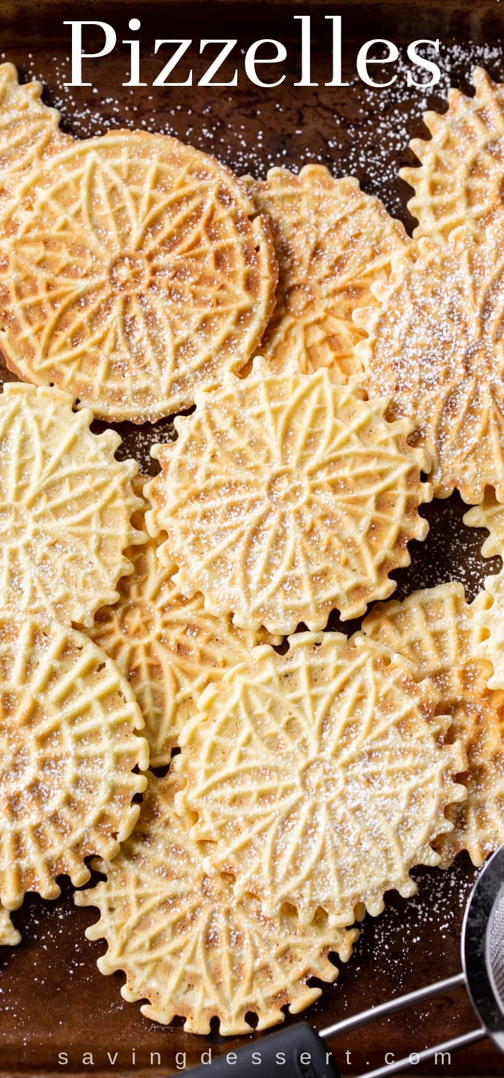 A baking tray covered with pizzelle cookies dusted with powdered sugar