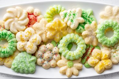 A platter of colorful Spritz Cookies made using a cookie press