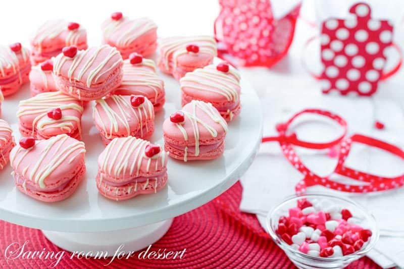 Raspberry Macarons - simple heart shaped macarons using the Italian method, with tips, tricks and how-to instructions for the best cookies. Filled with a fresh raspberry buttercream and topped with a drizzle of white chocolate. Great for Valentine's Day! www.savingdessert.com