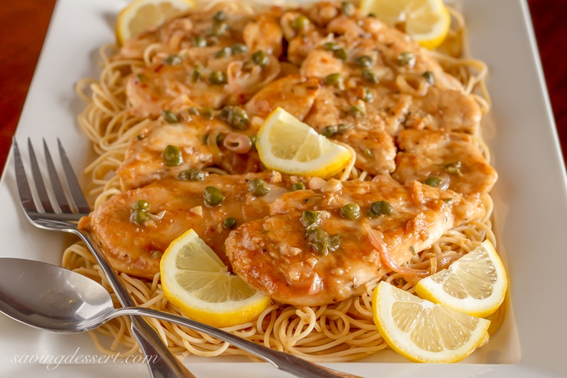 A platter of easy Chicken Piccata Recipe served with lemon wedges over hot spaghetti