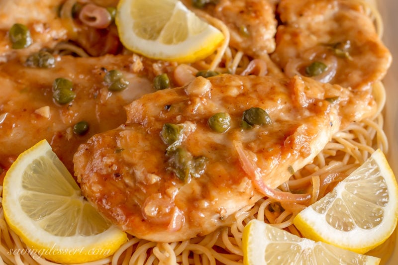 A closeup of chicken piccata with capers and lemon wedges served over spaghetti