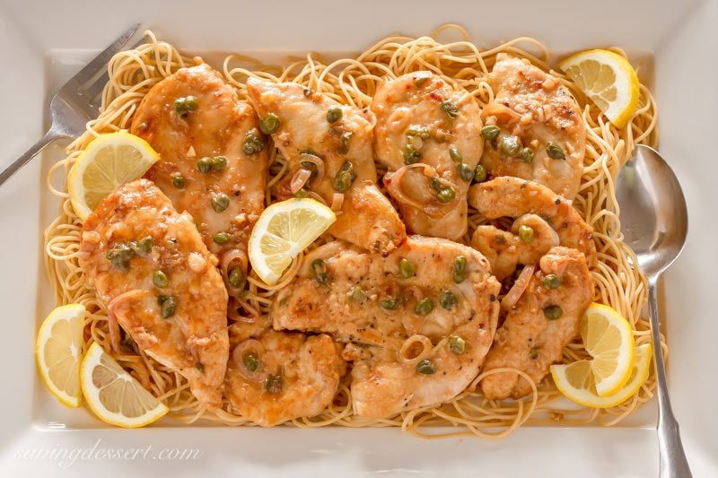 A platter of Chicken Piccata over spaghetti garnished with lemon wedges