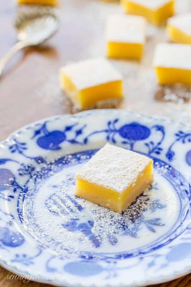 Tangy Lemon Bars ~ Tangy, tart, sweet, and creamy, with an incredible texture and a delicious shortbread crust. These bars are absolutely amazing! www.savingdessert.com