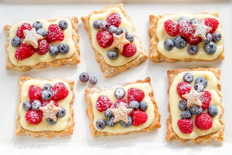Individual pastry tarts with vanilla cream topped with fresh berries and star cutouts