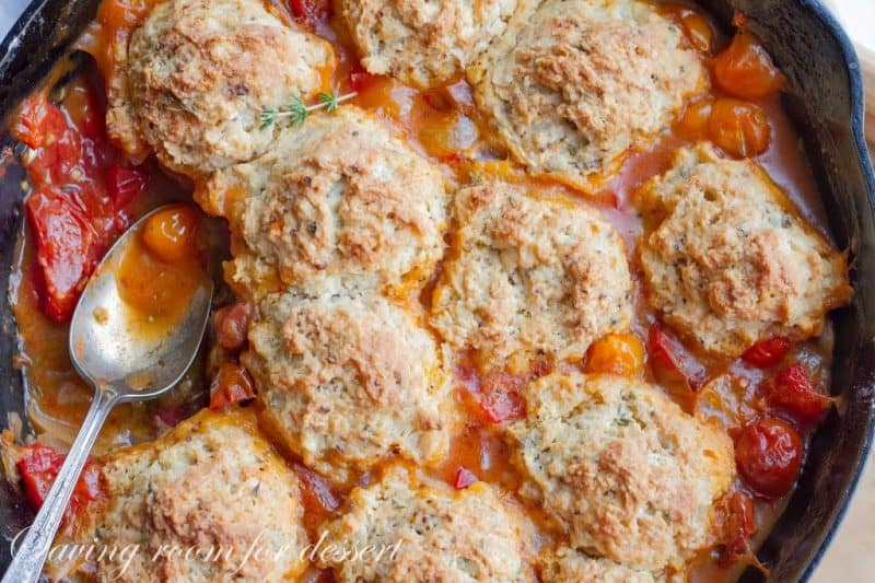 A skillet full of summer tomato cobbler with herbed biscuits on top