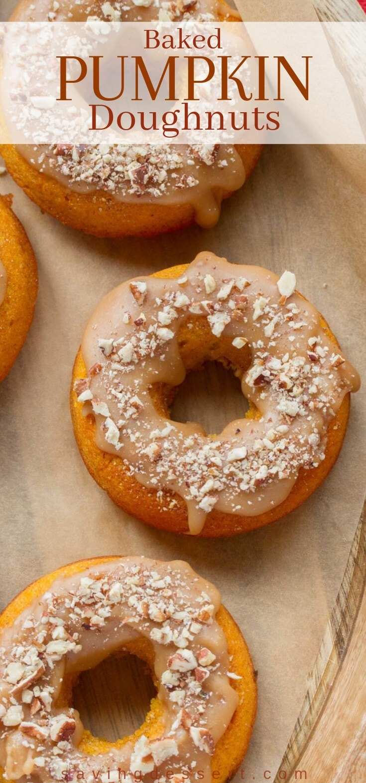 A tray of baked pumpkin doughnuts with caramel icing and chopped nuts