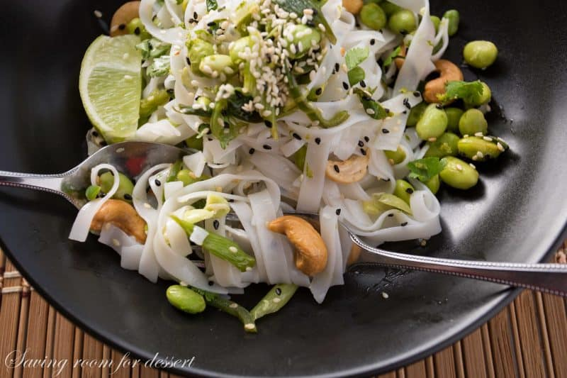 Rice Noodles with edamame and cashews - Sliced green onions and hot peppers are sautéed then tossed with a dressing of rice vinegar and sesame oil.  Add blanched edamame, sesame seeds, roasted unsalted cashews, garnish with chopped cilantro and lime zest then toss it all together with rice noodles and a squeeze of lime juice.  www.savingdessert.com