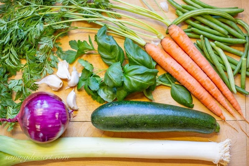 fresh carrots, green beans, a zucchini, garlic cloves, a red onion and a large leek piled on a cutting board with parsley and basil
