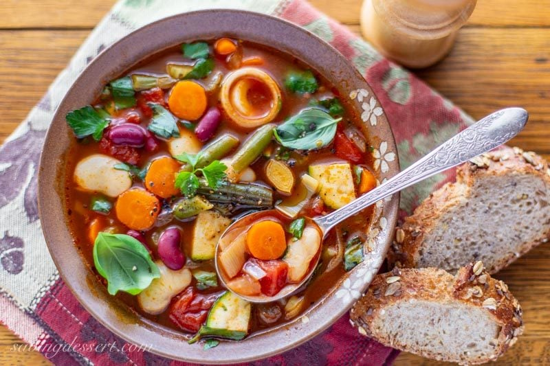 a bowl of chunky vegetable soup with beans and lots of fresh herbs.