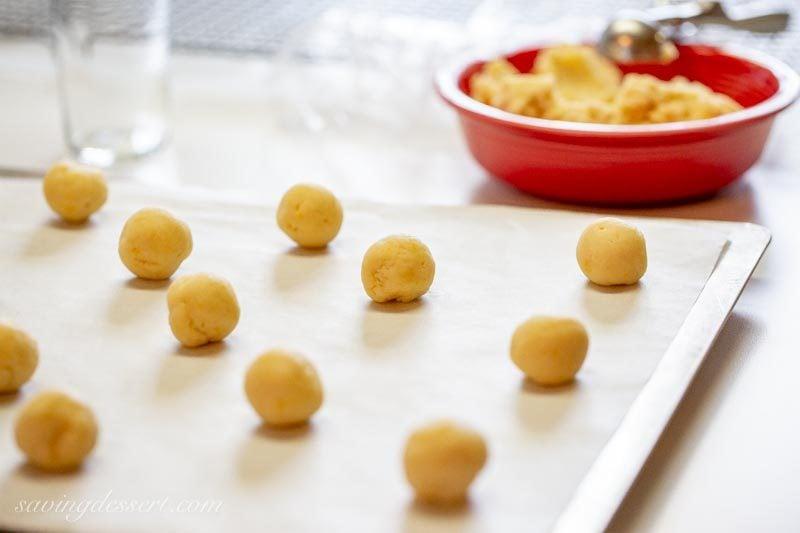 A wooden bowl of lemon meltaway cookies amongst icing on transcend Lemon Meltaways
