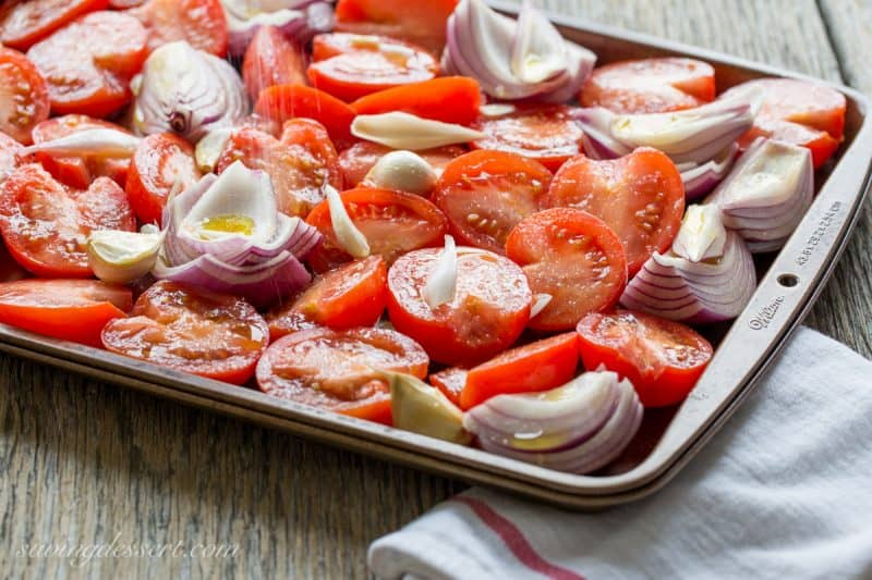 A pan of tomatoes, onion and garlic drizzled with olive oil