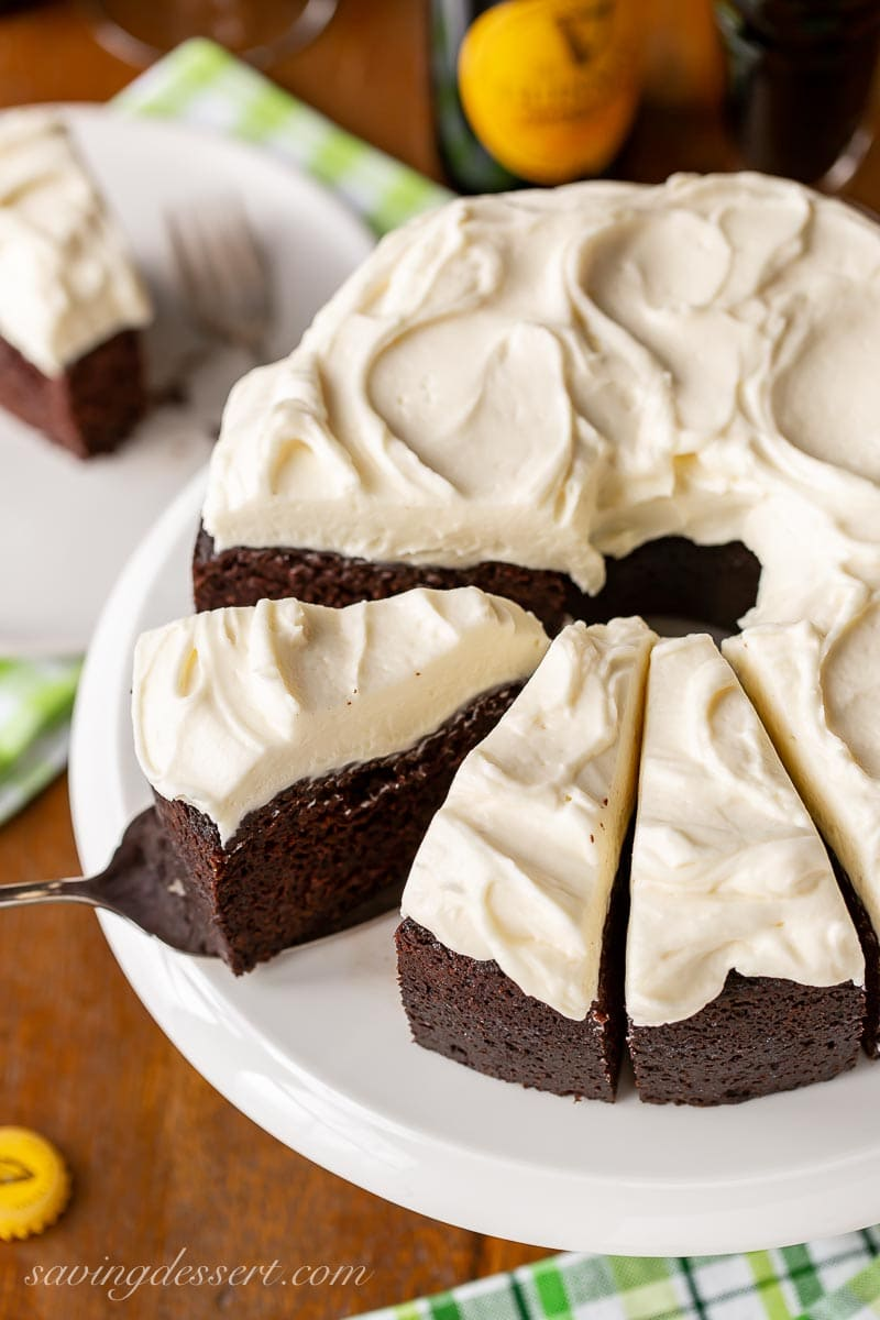 An overhead view of a sliced chocolate Guinness cake with cream cheese icing
