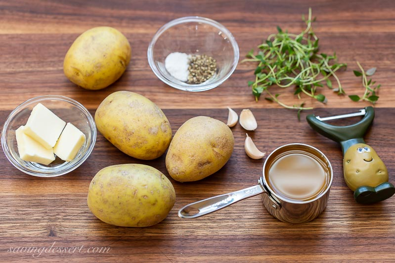 Cutting board with potatoes, butter, a peeler and fresh thyme