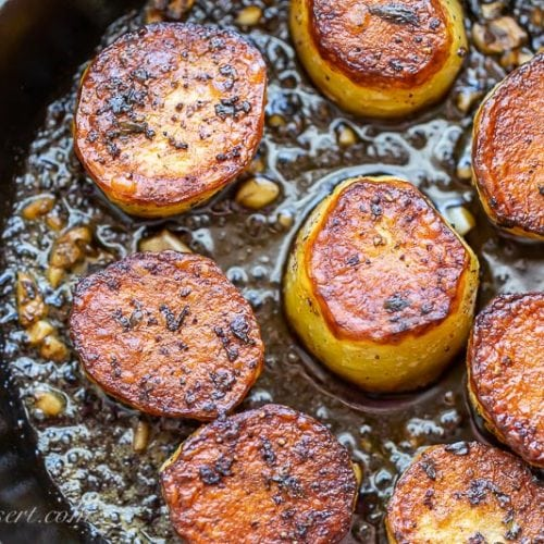 A cast iron skillet with crispy potatoes with garlic and thyme