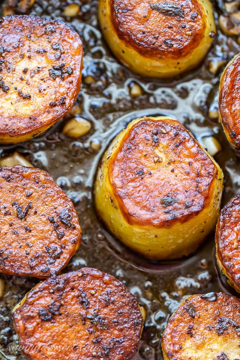 A close up of golden brown melting potatoes in a skillet with garlic