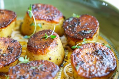 Close up of roasted potatoes with fresh thyme