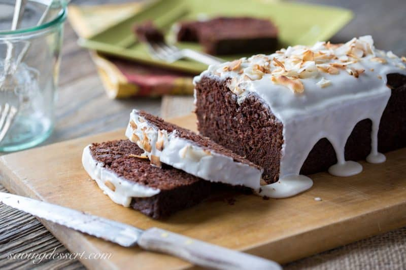 A sliced chocolate banana bread drizzled with a simple icing and toasted coconut