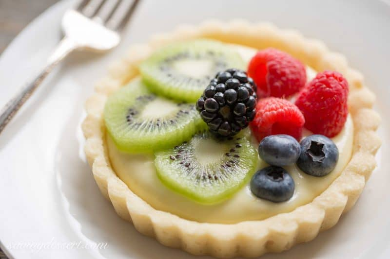Fresh Fruit Tarts -A light fresh fruit tart with a simple shortbread crust filled with a mixture of cream cheese and lemon curd. Super simple to make and easily adaptable to your favorite fruits.