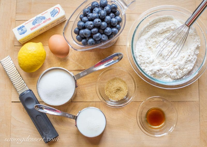 A cutting board with ingredients for a blueberry breakfast cake