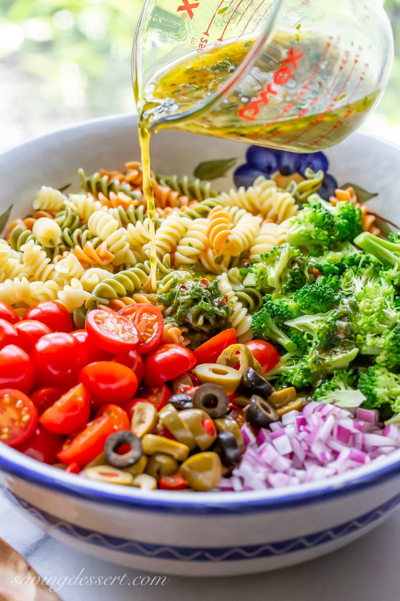 A bowl of cooked Rotini spiral noodles, broccoli, tomatoes, olives and red onion drizzled with a fresh zesty Italian dressing.