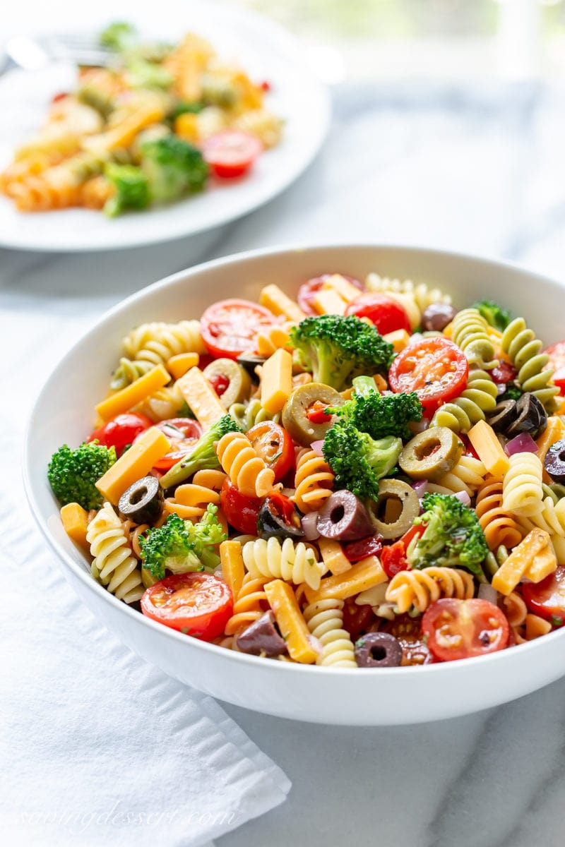A bowl of pasta salad with broccoli, tomatoes, cheese and olives