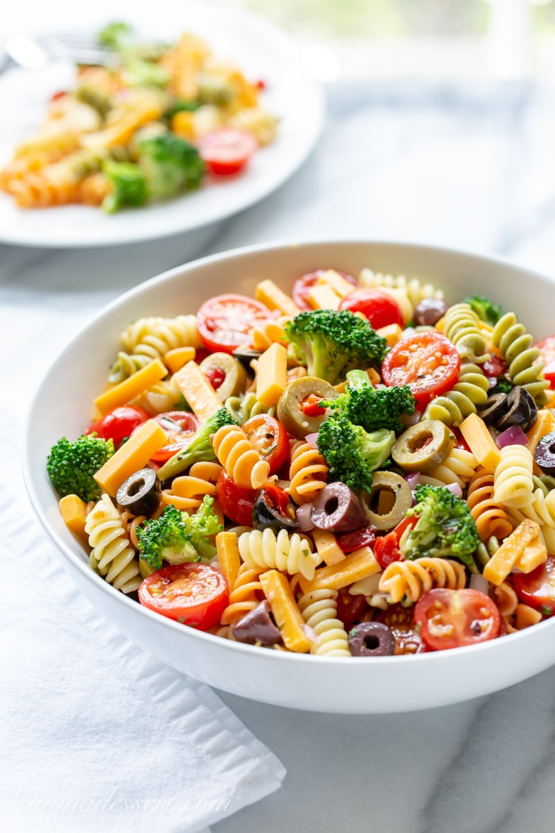 A bowl of pasta salad with cheese, olives, broccoli and tomatoes