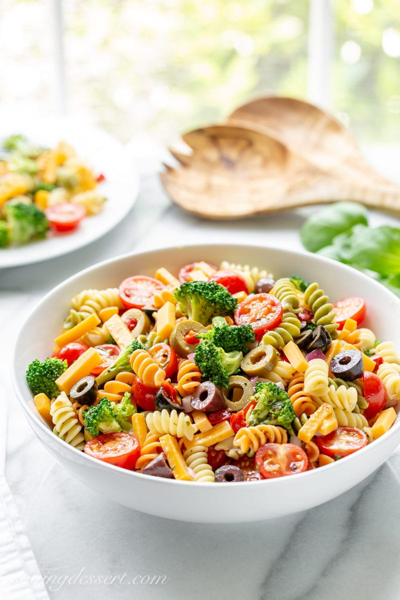 A bowl of summer pasta salad with Rotini spiral noodles, broccoli, cheese, olives and tomatoes