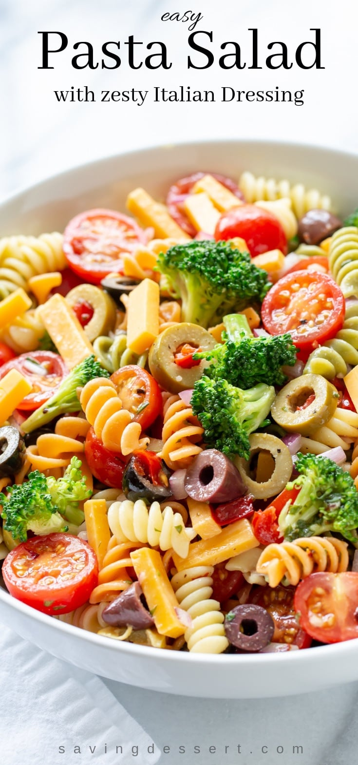 A large bowl of pasta salad with tomatoes, olives, broccoli and cheese